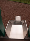 A close up shot of a metal slide in a child`s playground with ba Royalty Free Stock Photos