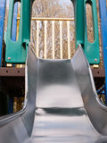 A close up shot of a metal slide in a child`s playground with ba Stock Photos