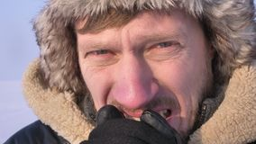 Close-up shot of middle-aged explorer in hood and coat freezing and trembling in cold and watching seriously into camera.  stock video footage