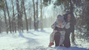 4K Winter games. Mother and child under the snowfall stock video footage