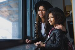 Close-up shot of mother and daughter in leather jackets looking. At window Stock Images