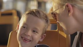 Boy with mum riding in the bus. Close-up shot of mother and son traveling by the bus in the city. Child is smiling when having a talk with mum during stock footage