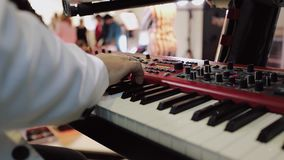Close up shot of musician playing keyboards. Musician Hands playing the piano. Fingers on the piano, colors lights stock footage