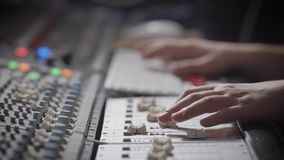 Close up shot of the musician`s hands, the professional records the music in the sound recording studio, the man moves