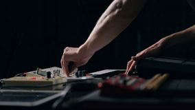 Musician plays keys and tunes synthesizer. Close up shot of musician`s hands play keys and tunes synthesizer stock footage