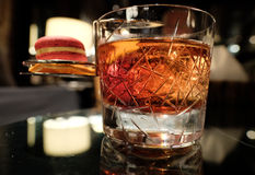 Close up shot of Negroni cocktail with campari macaroon Stock Image
