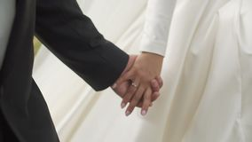 Close-up shot of the newlywed cou ple is softly holdign hands while walking. No face. stock video footage