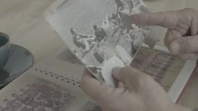 Close up shot of old woman hands pointing at young people on black white photograph in family photo album on wood table. Close up shot of old woman hands stock video