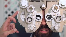 Close up shot of optometrist in white coat changing lenses on phoropter instrument and talking to male patient having