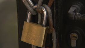 A padlock to a chain. A close up shot of a padlock that is locked to a chain stock footage