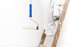 Close up shot of painter man at work climbing a ladder with pain Stock Images