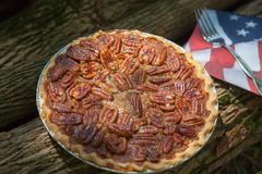 Close up shot of a pecan pie cooling. American classic homemade pecan pie. Amish pies. Napkin a flag of USA. stock photo