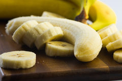 Close up shot of a peeled and cut banana on a wooden board Stock Image