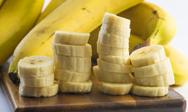 Close up shot of a peeled and cut columns of banana on a wooden board Stock Images
