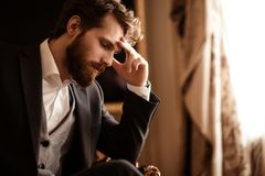 Close up shot of pensive bearded man in elegant formal suit, ponders about something, has some problems with finances stock images