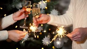 Close up shot of people hands, who celebrating new year, couple holding glasses with alcohol. Close up shot of a woman and a man`s hands who holds glasses with stock footage