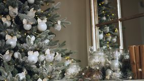 Close-up shot of perfect Christmas decoration mantel with accessories and green New Year tree with silver balls and