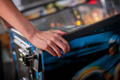 Close up shot of person playing with a pinball machine. Hand of female pressing button and playing pinball machine Royalty Free Stock Photography