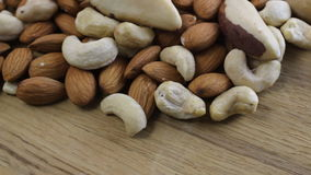 Close up shot of a pile of nuts rotating on wooden table stock video footage