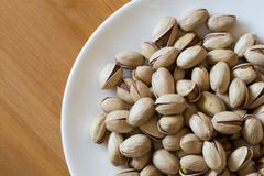 Pistachios in a white saucer container plate ready to be served and eaten. royalty free stock photos