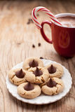 Close up shot of plate of peanut blossom chocolate cookies and hot chocolate in background Royalty Free Stock Image