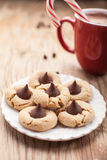 Close up shot of plate of peanut blossom chocolate cookies and hot chocolate on weathered brown wood Stock Image