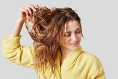 Close up shot of pleased female demonstartes her long cared natural hair wet after taking shower, being satisfied with new shampoo. Wears bathrobe, isolated Royalty Free Stock Photography