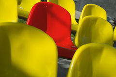 Close-up shot plenty of yellow and one red plastic seats at stadium Royalty Free Stock Photos