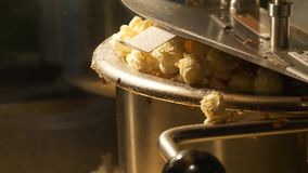 Close up shot of popcorn popping out of the pop corn machine. Video clip stock footage