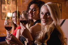 Close-up shot of positive beautiful female friends raising glasses of wine to happy event sitting in fashionable royalty free stock photography