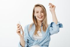 Close-up shot of positive carefree fair-haired female student in blue blouse, dancing with raised hands, holding. Smartphone and listening music in earphones Stock Photography