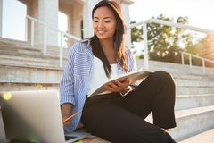 Close-up shot of pretty asian female student, using laptop, hold. Ing notebook, sitting on the city stairs on sunny day Stock Image