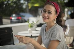 Close up shot of pretty brunette in round glasses outside. Stylish smiling model in red bandana with iPhone sits at table in open air cafe, copy space royalty free stock photos