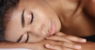 Close up shot of a pretty young wooman with smooth glowing skin relaxing on a white massage table. Royalty Free Stock Photography