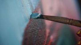 Close up shot of a paintbrush with oil paint, the artist creates a picture