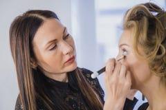 Close up shot. Professional make-up artist applying eyeshadow royalty free stock photos