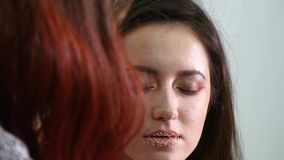 Close up shot. Professional make-up artist applying makeup on the face of the beautiful young sensual model.Beauty and. Close up shot. Professional make-up stock footage