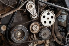 Close up shot of the pulley system and drive belt on a powerful diesel or gasoline used engine with parts of the car and vehicles royalty free stock image