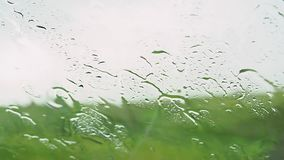 Close up shot of rain drops falling down. Close up shot of rain drops falling down a clear car window during a thundery rainstorm stock video footage