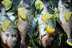 Close-up shot of raw fish with lemon ready for cooking. Sparus aurata. Concept of healthy food. Recipe of gilt-head bream fish.  Stock Photo
