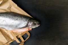 Close up shot of raw fresh rainbow trout on a black background on paper bag Preparations for cooking. Close up shot of raw fresh rainbow trout on a black Royalty Free Stock Photography
