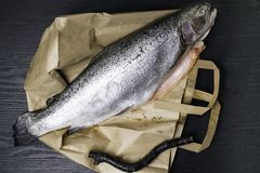 Close up shot of raw fresh rainbow trout on a black background on paper bag Preparations for cooking. Close up shot of raw fresh rainbow trout on a black Royalty Free Stock Photos