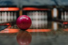 close-up shot of red bowling ball lying on alley under warm light stock images