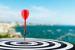 Close up shot red dart arrow on center of dartboard on city and. Close up shot red dart arrow on center of dartboard, metaphor to target success, winner concept Royalty Free Stock Photos