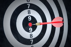Close up shot red dart arrow on center of dartboard Stock Image