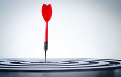 Close up shot red dart arrow on center of dartboard. Metaphor to target success, winner concept, shallow depth of field stock photos