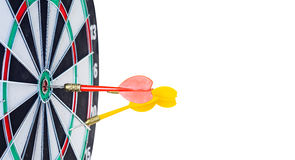 Close up shot red dart arrow on center of dartboard and yellow a. Rrow not hit the target with copyspace, metaphor to target success, Isolated on white Stock Photos