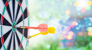 Close up shot red dart arrow on center of dartboard and yellow a. Rrow not hit the target with copyspace, metaphor to target success Royalty Free Stock Image
