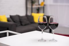 close-up shot of red wine on table in front of blurred living room stock photos