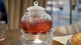 Close-up shot of a restaurant table and glass teapot warming up with a candle beneath.  stock video footage
